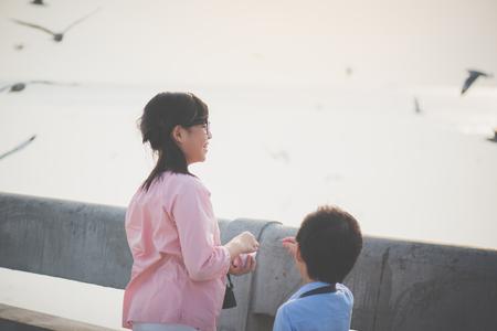 Asian children feeding the seagulls on the bridge, sunset time