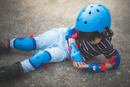 Asian child falls over while rollerblading in the park Foto de archivo