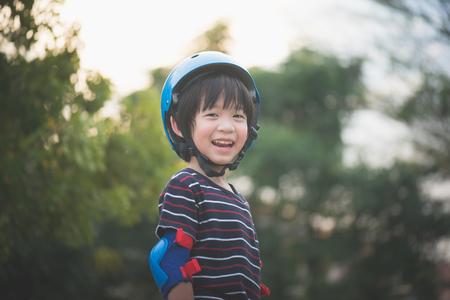 Retrato de niño feliz en casco azul de pie con fondo de naturaleza