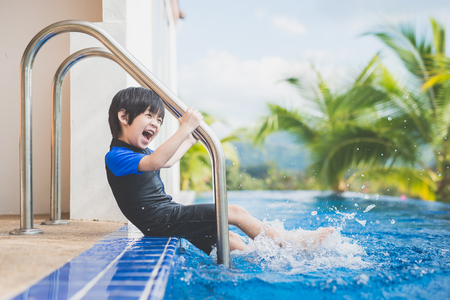 Asian child splashing around in the pool