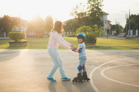 Asian mother helping her son to playing roller skate in the park Foto de archivo - 97985677