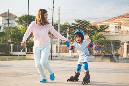 Asian mother helping her son to playing roller skate in the park Фото со стока - 97862849