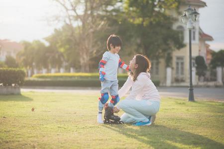 アジアの母親は、彼女の息子が公園で一緒に時間を楽しむために彼のローラースケートを置くのを助ける 写真素材