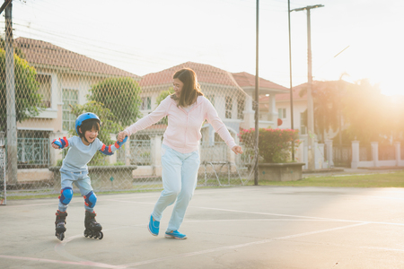 公園でローラースケートをする彼女の息子を助けるアジアの母親 写真素材