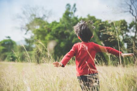 草原でパイロット飛行士を演じるアジアの子供の背中