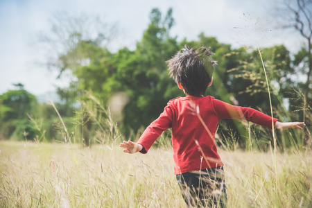 Back of  Asian child playing pilot aviator in the grass field Archivio Fotografico