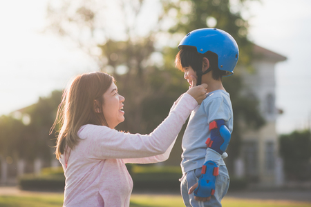 Asian mother helping her son wears blue helmet on enjoying time together in the park 스톡 콘텐츠