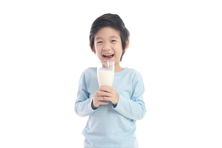 Asian child drinking milk from a glass on white background isolated Stockfoto
