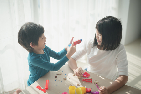 Asian children have a fun together with colorful modeling clay at home Stock Photo