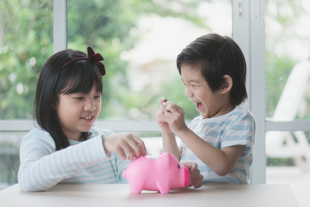 Cute Asian child putting a coin into a piggy bank