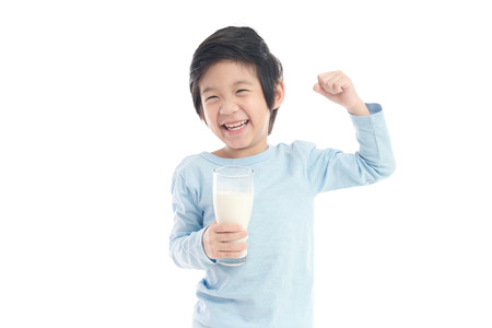 Asian child drinking milk from a glass on white background isolated Imagens