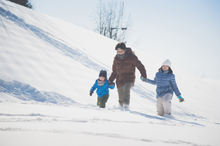 Asian father and his children holding hands and walking in the snow together Stock Photo