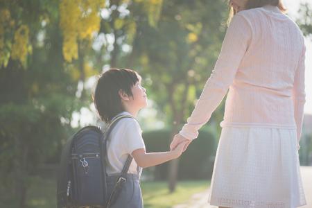 Asiatische Mutter, die Hand des kleinen Sohnes mit Rucksack im Freien hält, zurück zur Schule Standard-Bild