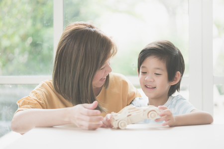 Asian mother and her son playing wooden car toy together Stockfoto