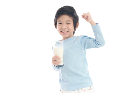 Asian child drinking milk from a glass on white background isolated Banco de Imagens