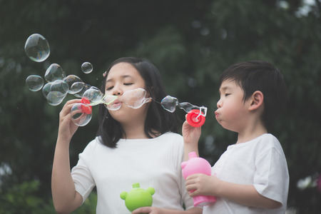 Cute asian children is blowing a soap bubbles,outdoors