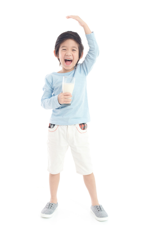 Asian child drinking milk from a glass and measuring himself  on white background isolated Archivio Fotografico - 101355046
