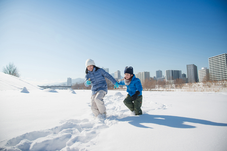 Cute Asian children playing on snow in the park together,Sapporo Hokkaido Japan