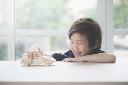 Cute Asian child playing wooden model car on a table Standard-Bild