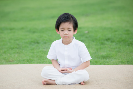 Asian child wearing white dress meditating in lotus position