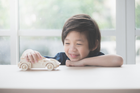 Cute Asian child playing wooden model car on a table