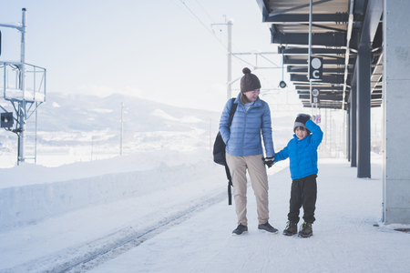 Asian mother and son waiting express train on railway station platform,winter travel concept