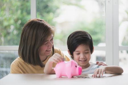 Enfant asiatique mignon mettant une pièce dans une tirelire