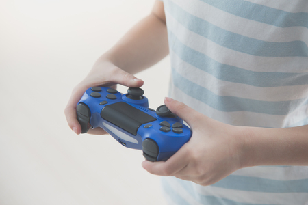 Asian child holding a game console controller playing video games. Stock Photo