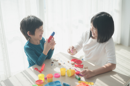 Asian children have a fun together with colorful modeling clay at home Stok Fotoğraf