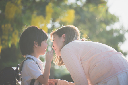 Asian child whispers something to his mother,back to school
