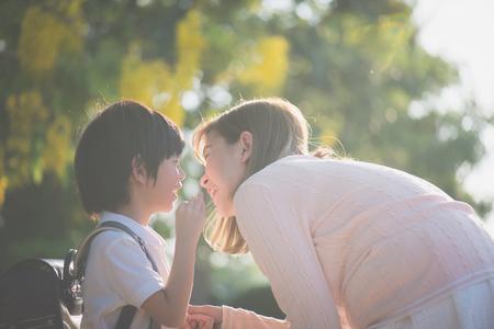 Niño asiático le susurra algo a su madre, regreso a la escuela
