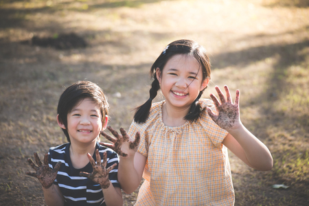 Happy Asian children playing outside with dirty hands Stock Photo