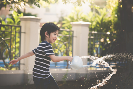 Cute Asian child watering in the garden on summer day