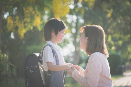 Asian mother  saying goodbye to her son as he leave for School,back to school concept 版權商用圖片 - 101362289