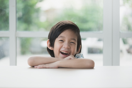 Cute Asian child sitting at table and smiling to the camera Stock Photo