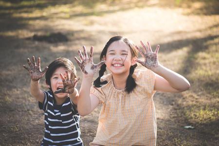 Glückliche asiatische Kinder, die draußen mit schmutzigen Händen spielen