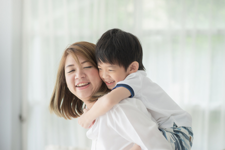 Asian child on a piggy back ride with his mother at home Banque d'images