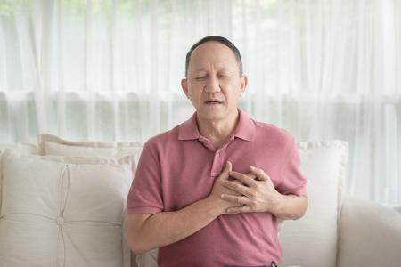 Uomo anziano asiatico con dolore al petto che soffre di infarto in casa