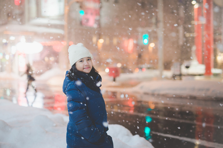 Beautiful asian girl girl in a night city snowflake ,Aomori Japan
