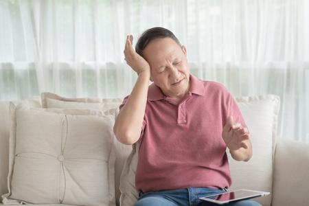 Vieil homme asiatique à la maison ayant un mal de tête