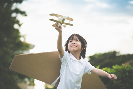 Cute Asian child playing wooden airplane in the park outdoors
