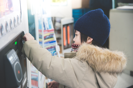 Cute Asian child purchasing soft drink from vending machine in the train station