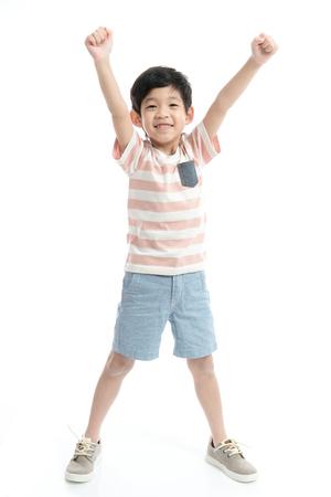 Leuk Aziatisch kind dat winnaarsteken op witte geïsoleerde achtergrond toont