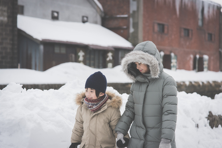 Cute Asian children holding hands and walking together at Otaru canal Hokkaido Japan