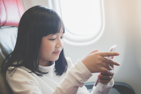 Beautiful Asian girl use of mobile phone inside airplane Imagens