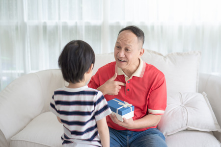 Cute Asian child giving a blue gift box for grand father