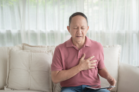 Asian old man with chest pain suffering from heart attack in home