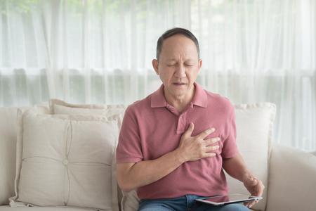 Uomo anziano asiatico con dolore al petto che soffre di infarto in casa Archivio Fotografico