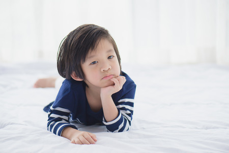 Portrait of unhappy asian baby lying on white bed Imagens