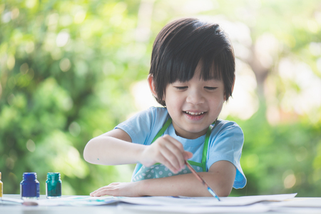 Cute Asian boy painting a picture